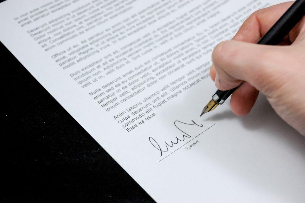 pessoa assinando um contrato com caneta