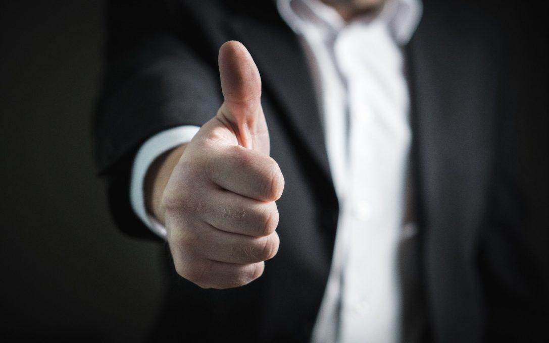 pessoa faz sinal de positivo com a mão